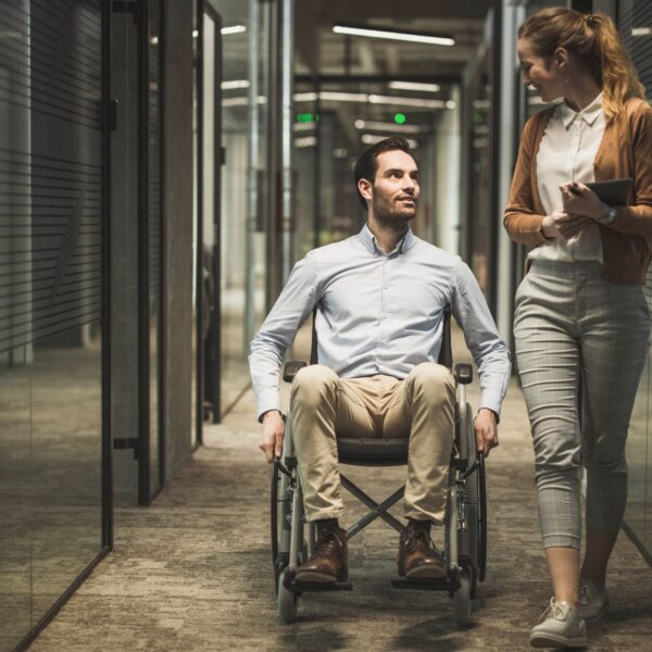 Man in a wheelchair with a woman in office